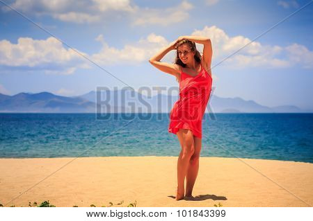 Blond Girl In Red Stands On Sand Beach Lifts Hands Over Her Head