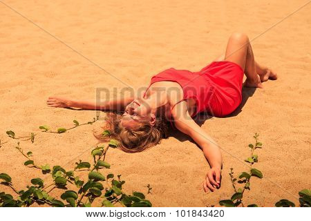 Upper View Blond Girl In Red Frock Lies On Sand With Hands Aside