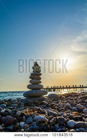 Turret Pebbles At Sunset With Ocean On Background And A Quay