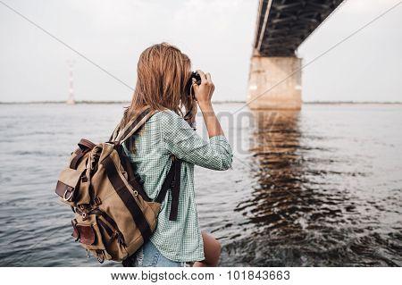 woman takes pictures a concrete car bridge