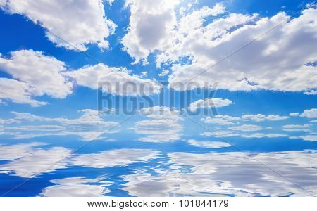 Blue sky with white clouds and reflection in water