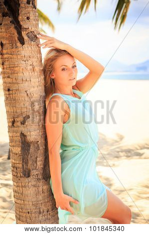 Blonde Girl In Transparent Frock Leans On Palm Trunk