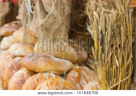 Ears Of Rye Grain And Freshly Baked Traditional Loaves Of Rye Bread On Stall