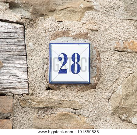 Number Twenty Eight On The Grey Stone Wall