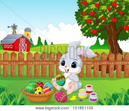 Cute Easter Bunny painting an egg in the garden