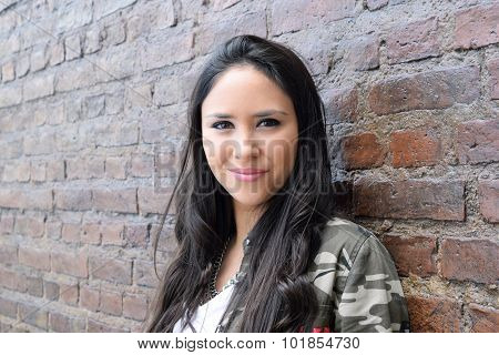 Hispanic Woman Against A Brick Wall.