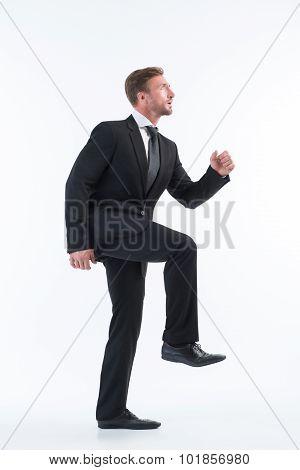 Businessman walking up imaginative stairs
