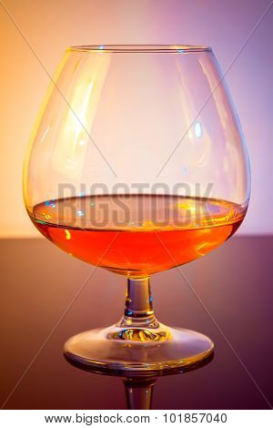 Snifter Of Brandy In Elegant Typical Cognac Glass On Colored Light Disco Background
