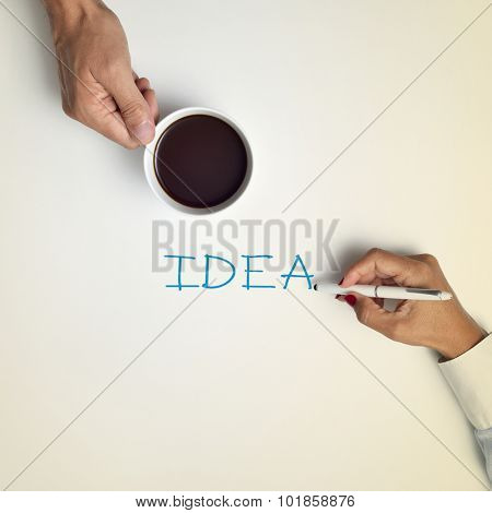 high-angle shot of a young man with a cup of coffee and a young woman writing the word idea with a pen