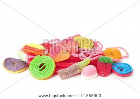 closeup of a pile of different candies on a white background