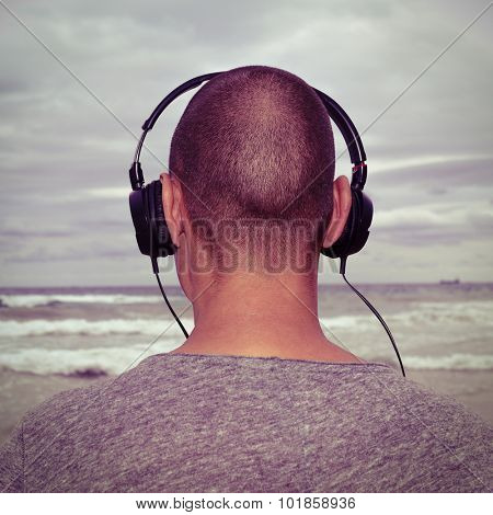 closeup of a young man seen from behind listening to music with headphones in front of the sea, with a filter effect