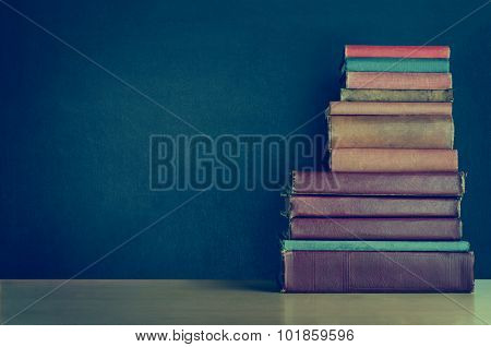 Book Stack On Desk With Chalkboard Background - Croos Processed