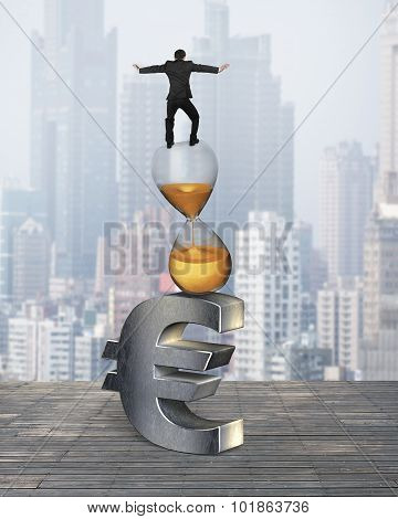 Businessman Balancing On Hourglass And Euro Sign