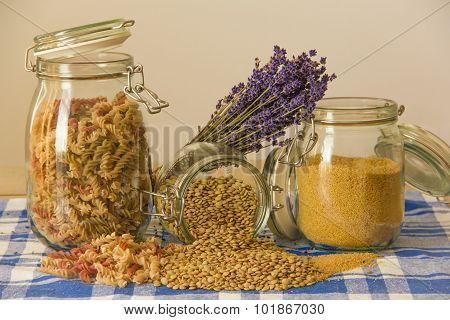 Three Jars With Pasta, Lentils And Couscous And Lavender On The Table.