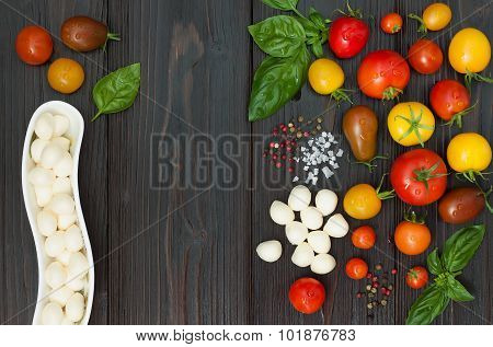 Cherry tomatoes of various color mozzarella basil leaves spices from above over dark wooden table. I
