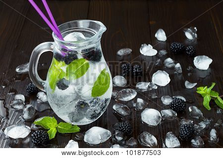 Healthy detox flavored water with blackberry and mint. Cold refreshing berry drink with ice on dark
