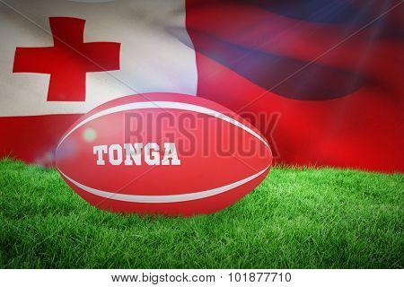 Tonga rugby ball against close-up of waving tonga flag