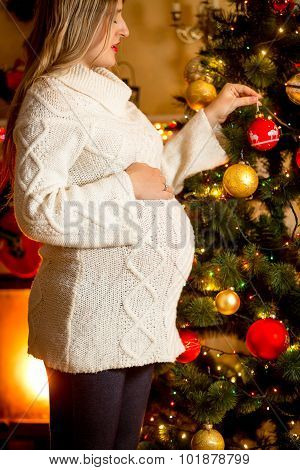 Closeup Of Pregnant Woman Decorating Christmas Tree At House