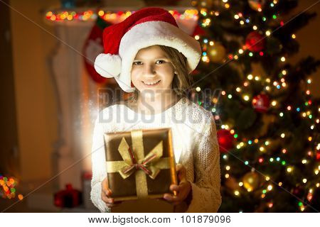Smiling Girl Posing With Shining Gift Box Against Christmas Tree