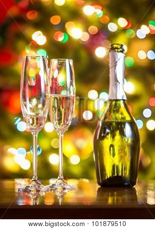 Champagne Flutes And Bottle On Table Against Christmas Lights