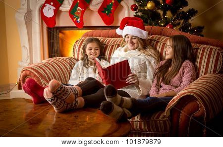 Woman Reading Book To Daughters On Sofa At Fireplace At Christmas