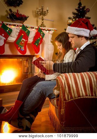 Father Sitting With Daughter At Fireplace And Telling Story
