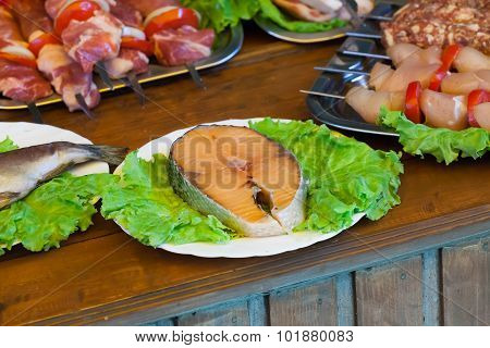 stake of a salmon  white plate with greens