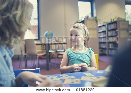 Education And Fun. Kids With Teacher Playing Games In Classroom Scenery