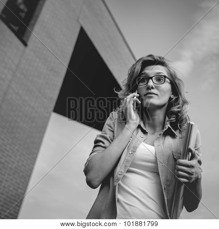 Young Businesswoman With Angry Or Upset Expression On Face Calling On Mobile Phone Holding Laptoip I