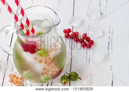 Healthy detox berry infused flavored water. Summer refreshing homemade drink with gooseberries and w