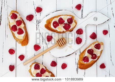 Italian bruschetta or crostini with raspberry, almond, goat cheese and honey on grilled crusty bread