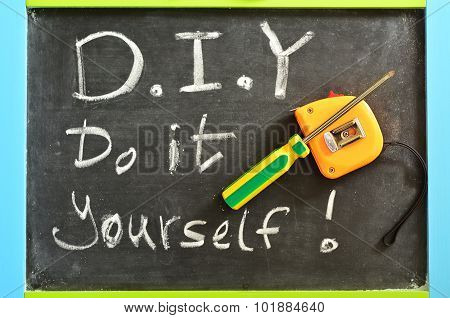 Do It Yourself - D.I.Y Handwritten with white chalk on a blackboard with working tools.concept photo of Do It Yourself.