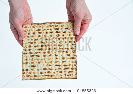 Jewish woman hands holds leavened bread matza on white background with copy space