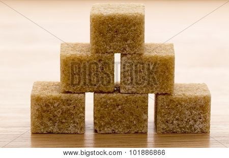 Brown cane sugar cubes on wooden background.Macro