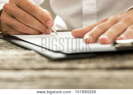 Low Angle View Of Male Hand Signing Contract Or Subscription Form