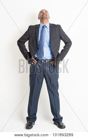 Full body mature Indian business man hand on waist and looking up, standing on plain background.