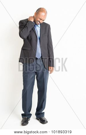 Full length Indian businessman shoulder pain, holding his neck with painful face expression, standing on plain background.