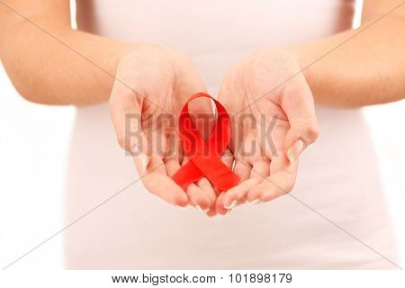 Female hands holding red ribbon sign, closeup