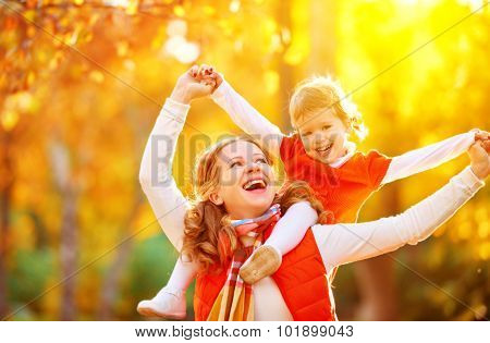 Happy Family: Mother And Child Little Daughter Play Cuddling On Autumn