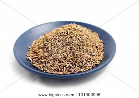 Macro Cumin Seeds On Blue Plate