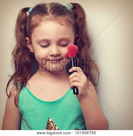Fun Beautiful Small Kid Girl Applying Tonal Cosmetic On The Face Using Makeup Brush. Closeup