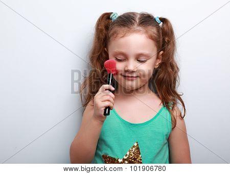 Fun Beautiful Small Kid Girl Applying Tonal Cosmetic On The Face Using Makeup Brush