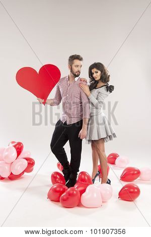 Young Smiling Caucasian Couple Holding Sign In Form Of Red Heart