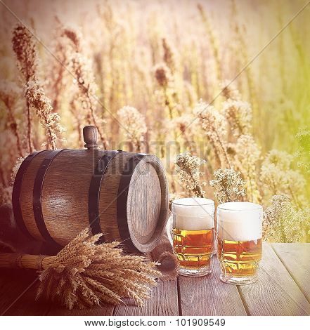 Beer barrel with beer glasses on table on field background