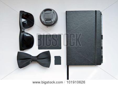 Business workplace with glasses, tie, business card, memory card and notebook on white background