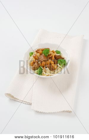 plate of chinese noodles with roasted meat and cashews on white place mat