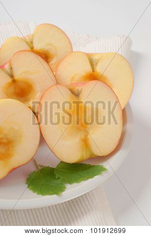 close up of halved and seedless apples on white plate