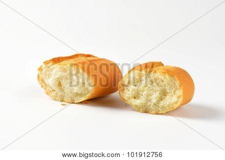 halved fresh bread roll on white background