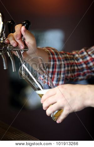 Bartender is pouring beer into glass
