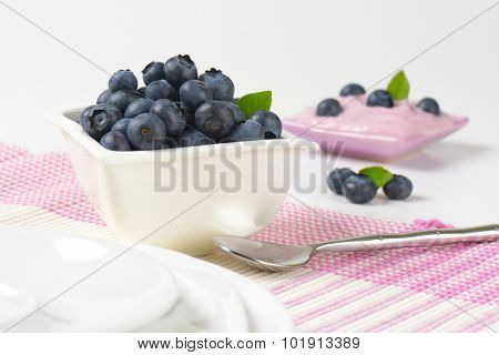 laid table with bowl of fresh blueberries